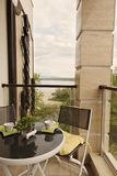 Beautiful terrace or balcony with table with coffee cups and flower on it and chairs. Balcony with sea view surrounded by nature. Hot summer day stock photos