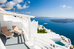 Beautiful terrace with chaise lounges, sea view. White architecture on Santorini island, Greece royalty free stock photography