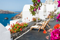 Beautiful terrace with flowers overlooking the sea. White architecture on Santorini island, Greece stock photography