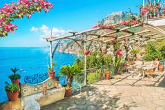 Beautiful terrace with sea view. Beautiful terrace with table, chairs and blooming flowers with view of sea and mountains near Positano, Amalfi coast, Italy royalty free stock photography