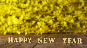 Beautiful text from wooden letters. Happy new year on a wooden background with a golden blur bokeh for the new year Royalty Free Stock Photo