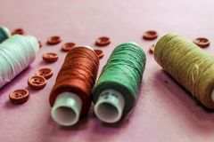 Beautiful texture with lots of round red buttons for sewing, needlework and skeins of spools of thread. Copy space. Flat lay. royalty free stock photography