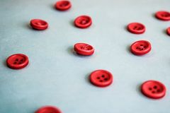 Beautiful texture with many round red buttons for sewing, needlework. Copy space. Flat lay. Blue background royalty free stock images