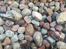 A beautiful texture of multi-colored round and oval natural solid stone stones, boulders, cobblestones under the blue water, under. Water view of the sea, the royalty free stock image