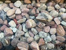 A beautiful texture of multi-colored round and oval natural solid stone stones, boulders, cobblestones under the blue water, under. Water view of the sea, the royalty free stock photography