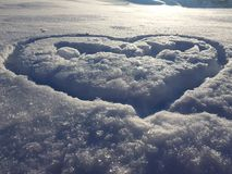 Beautiful texture of snow cover and heart stock photography
