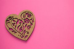 Beautiful textured poker-drawing wooden heart on pink background with copyspace as a symbol of love, Valentine`s day, greeting royalty free stock photography