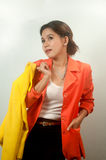 Pretty Asian business woman holding yellow suit . Royalty Free Stock Photography