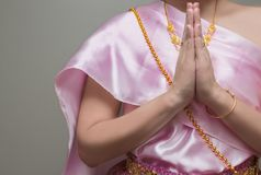 Beautiful Thai girl in traditional dress costume,press the hands together at the chest. Sawasdee royalty free stock image