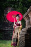 Beautiful Thai girl in traditional dress costume red umbrella as. Thai temple where is the public place, Thai Woman in Traditional Costume of Thailand royalty free stock image