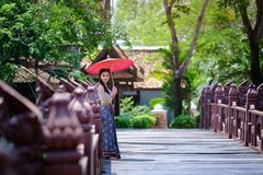 Beautiful Thai girl in traditional dress costume red umbrella as Royalty Free Stock Photos