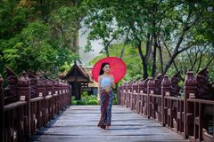 Beautiful Thai girl in traditional dress costume red umbrella as. Thai temple where is the public place on the wooden bridge royalty free stock images