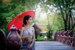 Beautiful Thai girl in traditional dress costume red umbrella as stock photos