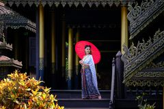 Beautiful Thai girl in traditional dress costume red umbrella as. Thai temple where is the public place stock photography