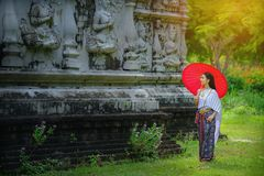 Beautiful Thai girl in traditional dress costume red umbrella as. Thai temple where is the public place, Thai Woman in Traditional Costume of Thailand stock image