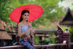 Beautiful Thai girl in traditional dress costume red umbrella as. Thai temple where is the public place stock images