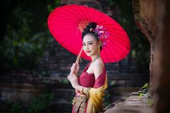 Beautiful Thai girl in traditional dress costume red umbrella as. Thai temple where is the public place, Thai Woman in Traditional Costume of Thailand stock images