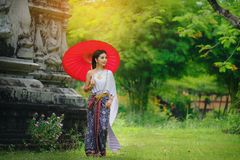 Beautiful Thai girl in traditional dress costume red umbrella as. Thai temple where is the public place, Thai Woman in Traditional Costume of Thailand stock photos