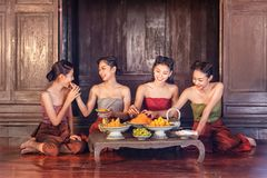 Beautiful thai girls in thai traditional costume and enjoy eating thai dessert. Thailand royalty free stock images