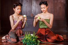 Beautiful Thai girls in thai traditional costume trying to roll up lotus flower stock photography