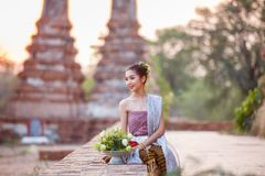 Beautiful Thai girls in thai traditional costume trying to roll up lotus flower at sunset time stock photo