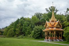Beautiful Thai pavilion with green trees and cloudy sky. Lausanne, Switzerland royalty free stock images