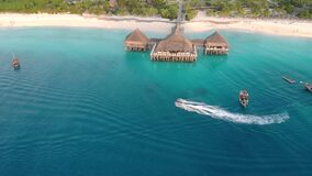 Beautiful thatch stilt house at Zanzibar Nungwi beach at evening time with blue Indian ocean aerial view