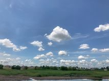 Thick fluffy clouds and grass field. Beautiful thick fluffy clouds and grass field Royalty Free Stock Photos