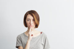 Beautiful, thin girl puts a finger to his lips, a sign of silenc Royalty Free Stock Image