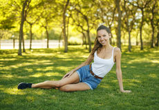 Beautiful thin girl sitting on the grass. Beautiful caucasian thin girl sitting on the grass and smiling summer day looking at camera. Perfect shape Royalty Free Stock Image