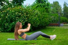 Woman training in the park. Beautiful thin woman sportswoman doing the exercise, swinging the press on a yoga mat before training on a green lawn in the park on stock photo