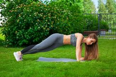 Woman training in the park. Beautiful thin woman sportswoman doing the exercise, swinging the press on a yoga mat before training on a green lawn in the park on stock photography