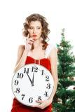 Beautiful thinking christmas girl holding clock Royalty Free Stock Image