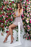 Beautiful thinking romantic woman with long hair posing and sitting in fashion summer dress and trendy silver shoes on bright flo royalty free stock images