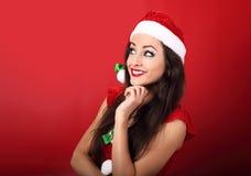 Beautiful thinking smiling woman in santa claus christmas costum Stock Photos