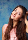 Beautiful thinking student girl looking up on blue Royalty Free Stock Images