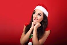 Beautiful thinking woman in santa claus christmas costume lookin Royalty Free Stock Photo