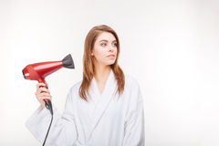 Beautiful thoughful woman in bathrobe drying her hair with dryer Royalty Free Stock Photos