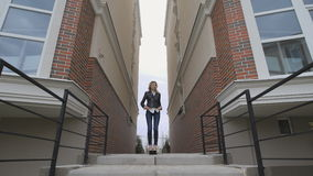 Beautiful thoughtful blond woman stands between two houses. wide angle stock video
