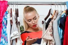 Beautiful thoughtful blonde woman standing inside wardrobe rack Royalty Free Stock Photo