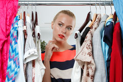 Beautiful thoughtful blonde woman standing inside wardrobe rack Stock Photos