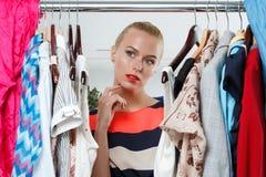 Beautiful thoughtful blonde woman standing inside wardrobe rack Stock Photos