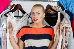 Beautiful thoughtful blonde woman standing inside wardrobe rack Royalty Free Stock Photography