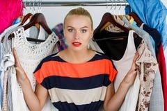 Beautiful thoughtful blonde woman standing inside wardrobe rack Stock Photo