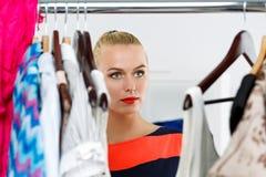 Beautiful thoughtful blonde woman standing inside wardrobe rack Royalty Free Stock Photos
