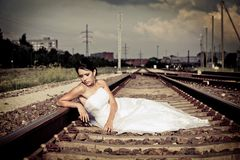 Beautiful thoughtful brunette bride is sitting on the railway and waiting Stock Photography