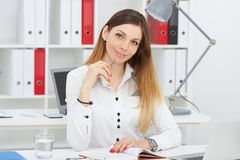 Beautiful thoughtful business woman sitting at office workplace looking at the camera. Serious business and partnership, job offer, financial success Stock Photography