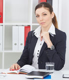 Beautiful thoughtful business woman sitting at office workplace looking into the camera. Serious business and partnership, job offer, financial success Stock Photos