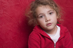 Beautiful thoughtful child. On red Royalty Free Stock Photography
