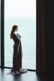 Beautiful thoughtful female with long hair standing in knitted coverlet Stock Photos